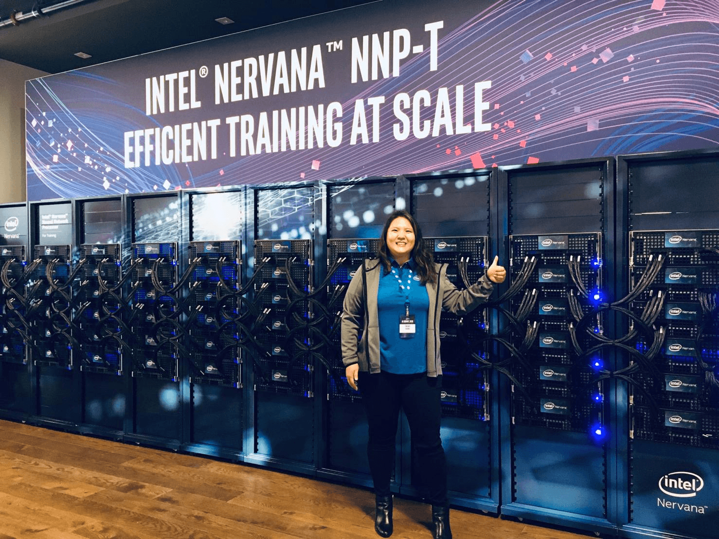 Tingwei Huang, Director of Product Management for Intel's AI Products Group, stands in front of a 10-rack Intel AI system powered by 480 Intel Nervana NNP-T chips
