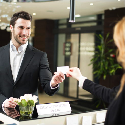 Man-Gives-Card-To-Woman-At-Hotel-Desk.png