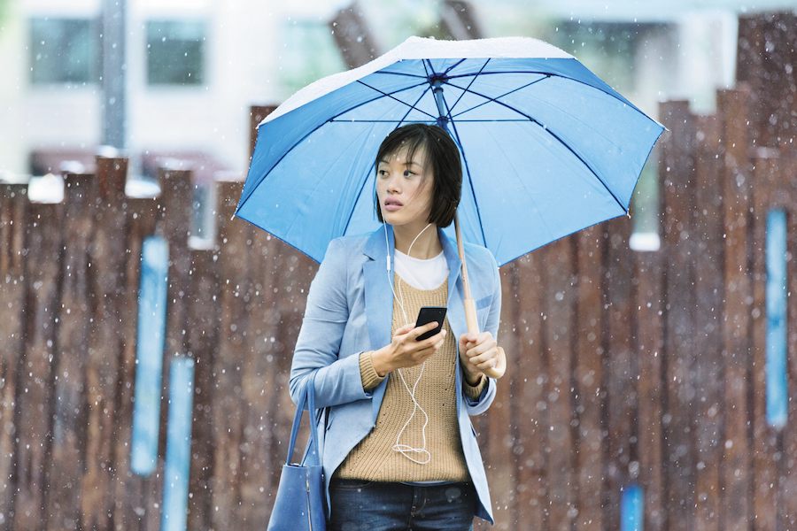 Woman-Holding-Umbrella-Using-Mobile-Phone.png