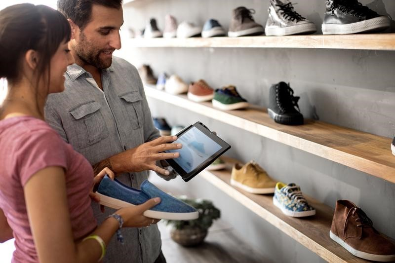 man-helping-woman-in-retail-store-using-mobile-device.jpg