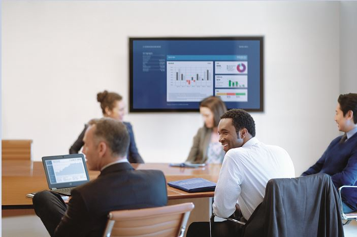 A group of people sit around a conference room table. Behind them on the wall is a monitor displaying analytics.