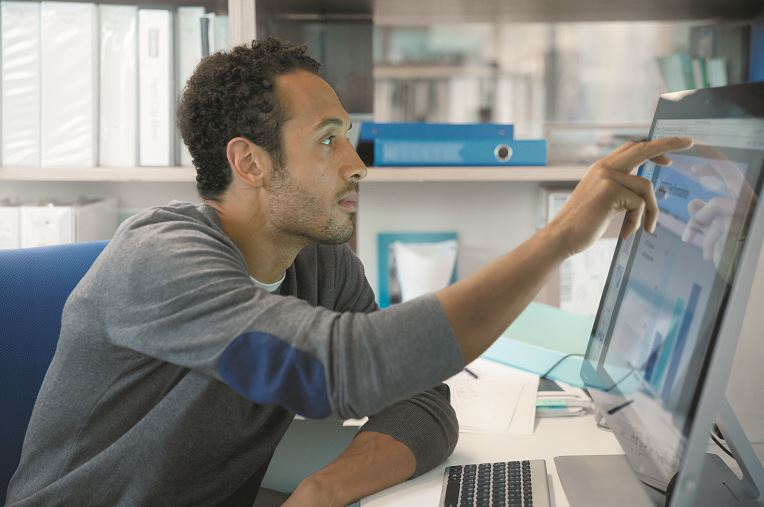 A man taps a monitor with his middle and index fingers.