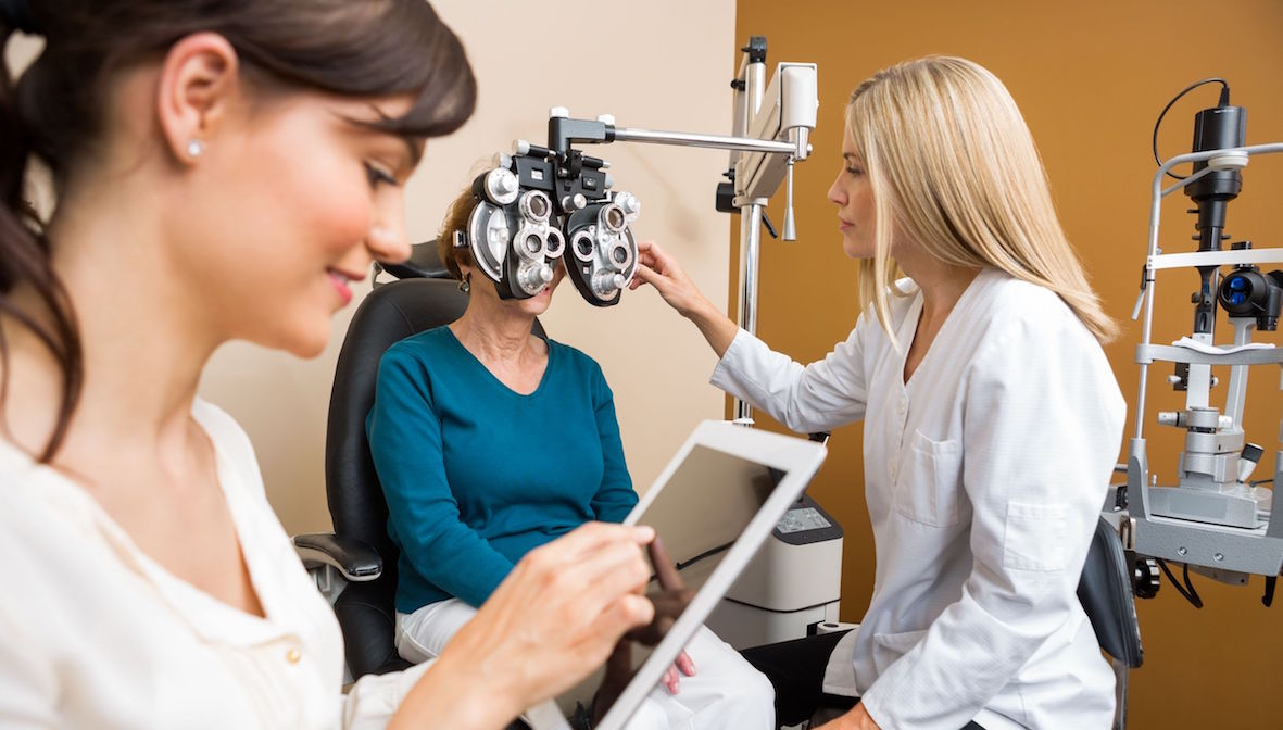 23724610 - female optometrist examining senior woman's eyes while colleague using digital tablet in store