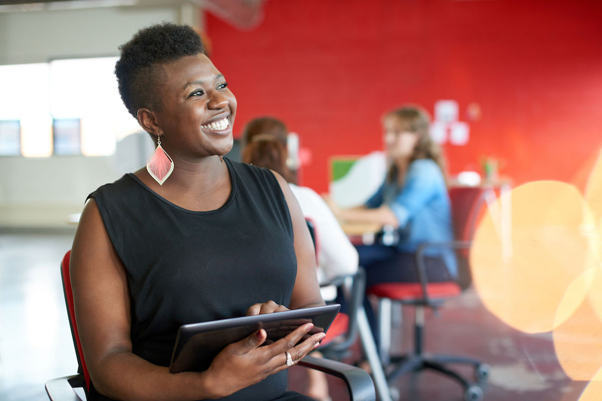 casual african american business woman using tablet technology in a bright startup office