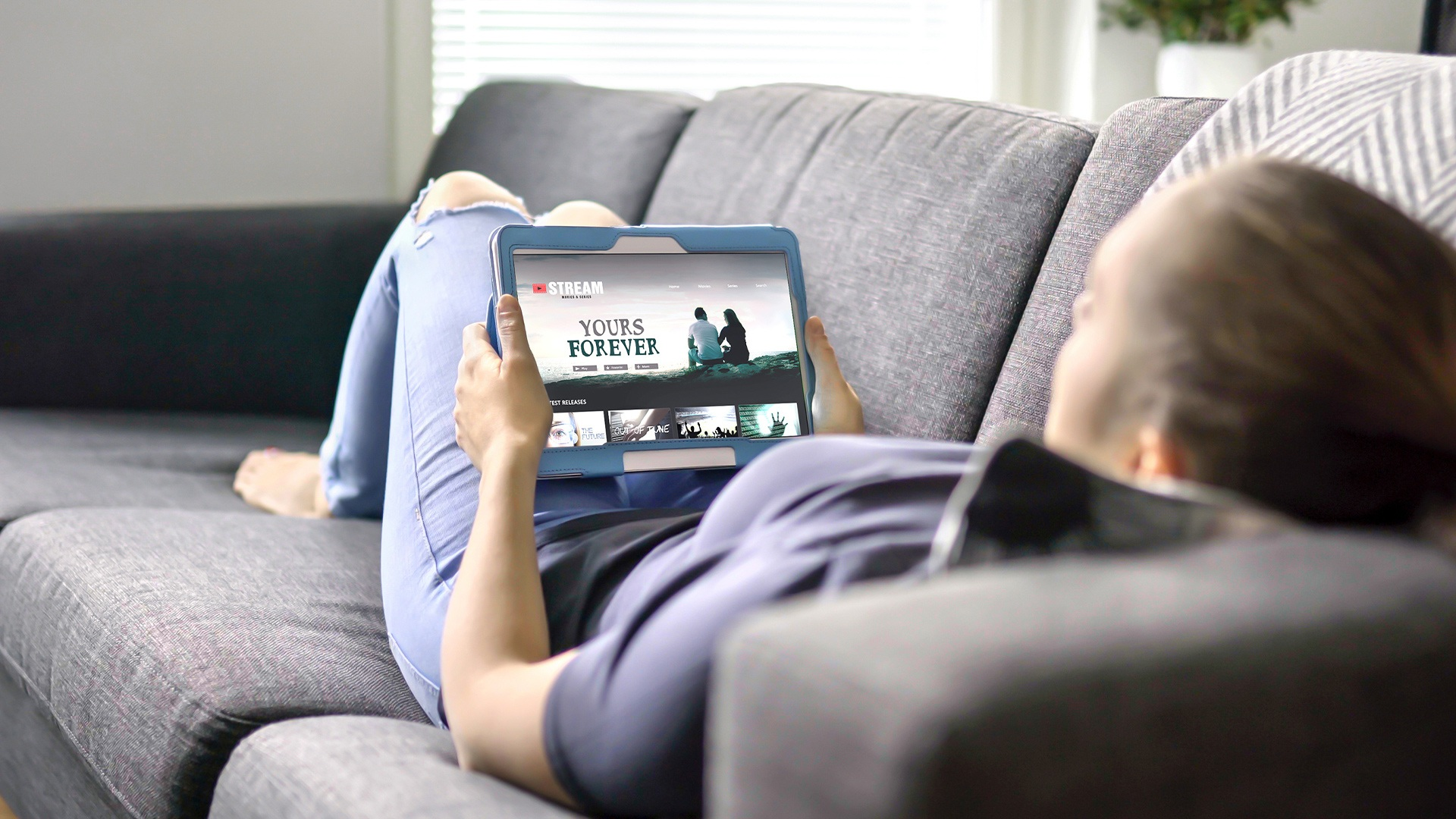 Woman lying on a sofa watching a streaming video on her tablet device, conveying how AV1 codec is used.