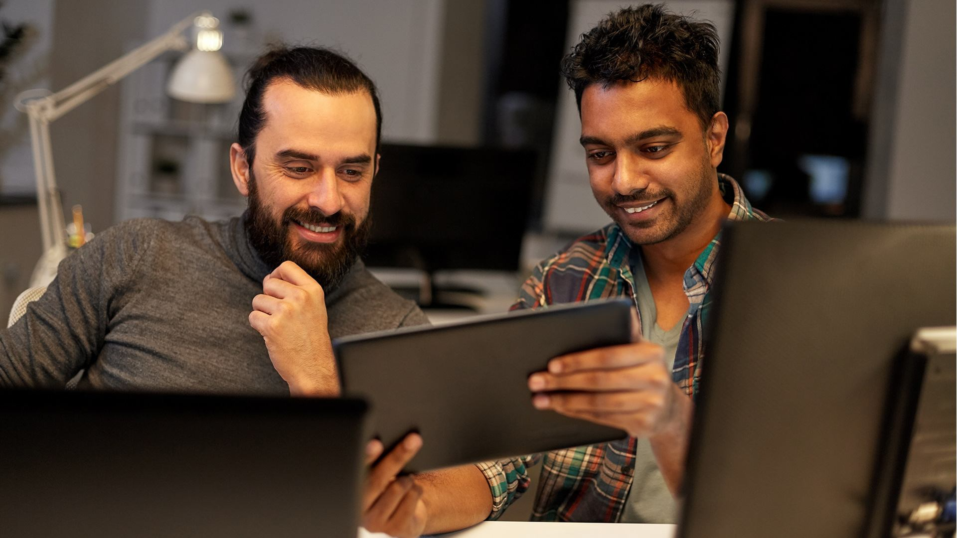 Two people at work smiling, looking at a tablet