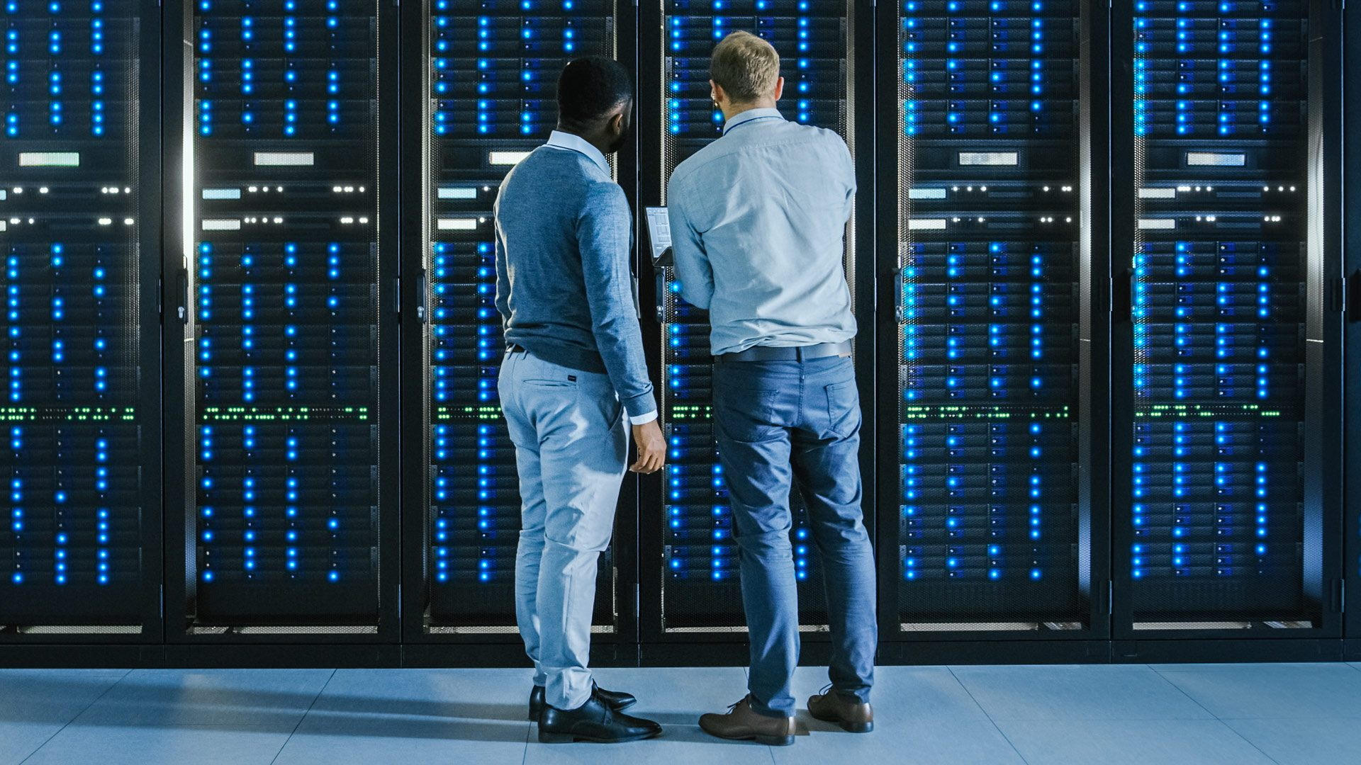 Two people standing in front of a generic server rack meant to convey AWS.