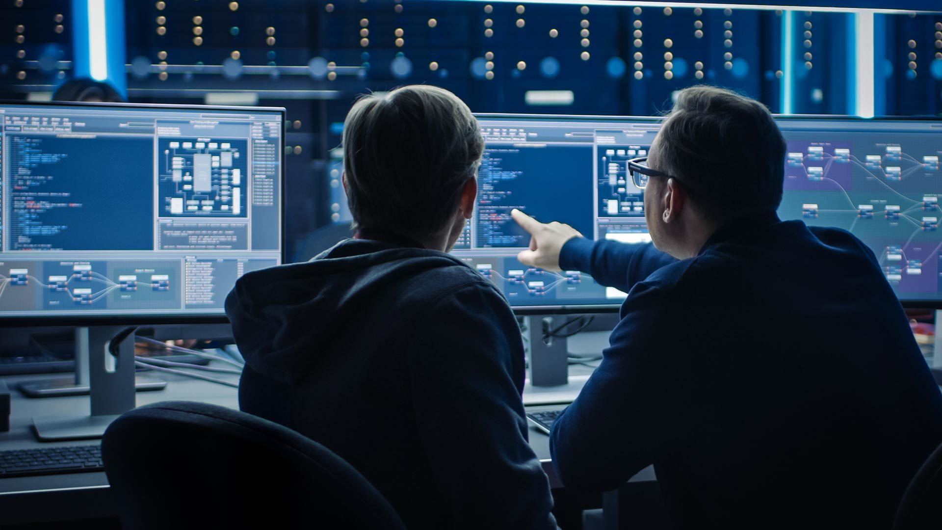 Two people looking at three monitors pointing to the screen representing the DeepMind team doing AI research.