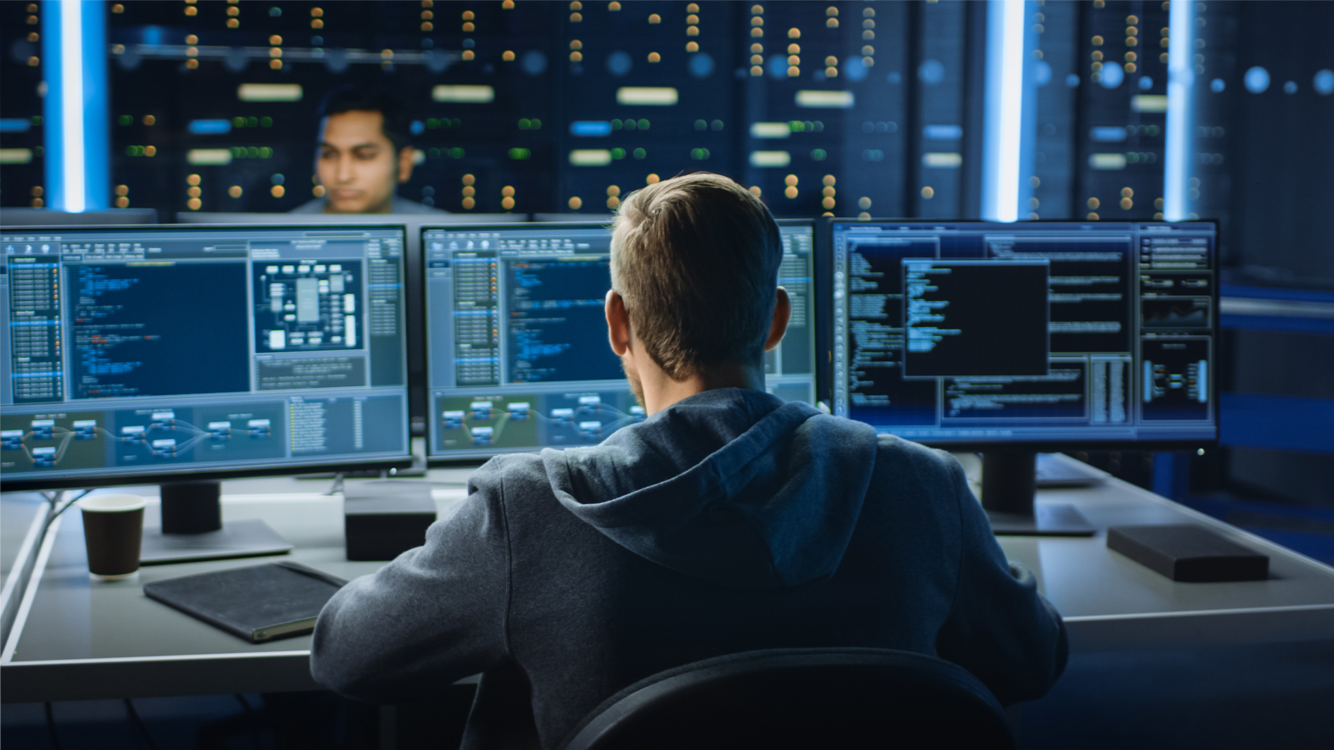 Image of a person in a data center control room looking at lines of code on a computer screen meant to be AWS Red Hat OpenShift console