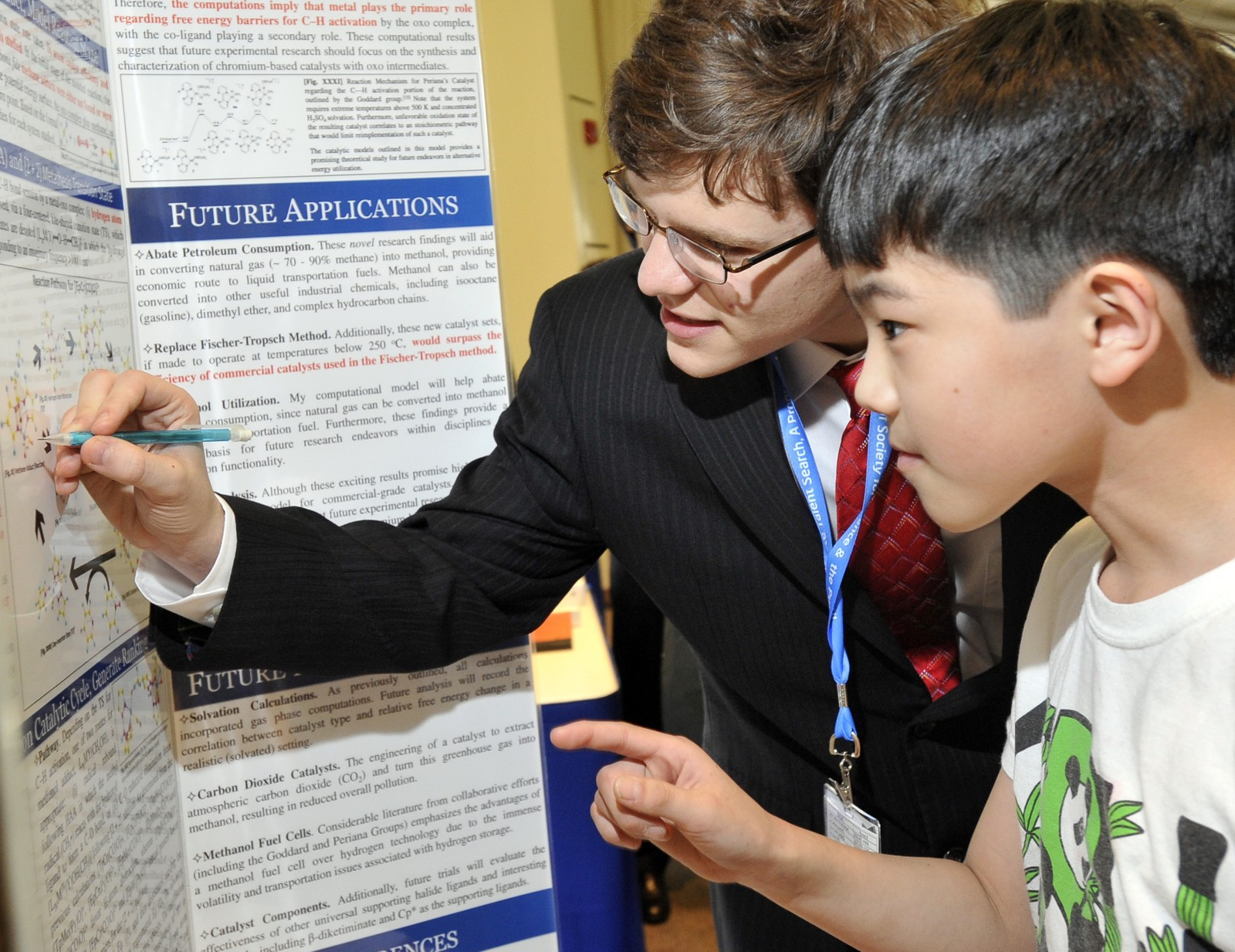 Kurtis Carsch, 17, of Plano, Tex. discusses with a curious young man his research, which could result in cleaner, lower-cost fuel.